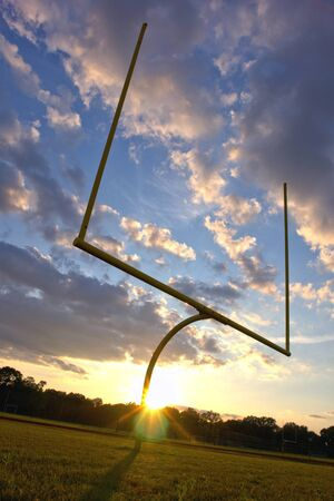 American football goal posts at sunset over dramatic sky photo