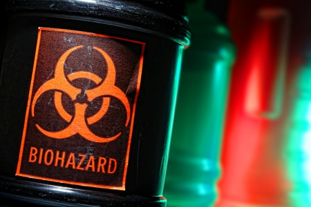 hazardous: Grunge biohazard universal symbol danger warning label on a dangerous toxic waste black container in a scary hazardous material disposal site