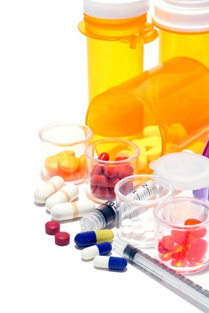 Prescription medicine pills and sample medication drug tablets in high dosage with syringes and pharmaceutical amber bottles for an aggressive medical treatment regimen to treat and cure a disease Stock Photo