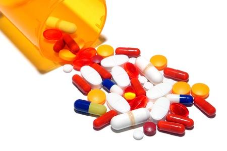 sobredosis: Generico pastillas medicaci�n medicina derramado de una botella de color �mbar farmac�utica como una met�fora de un c�ctel de drogas y sobredosis peligrosa Foto de archivo