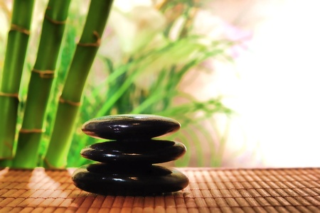 Polished black hot massage stones cairn on a natural mat over floral and bamboo plant background in a relaxation spa