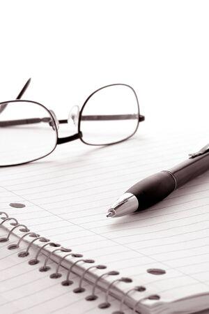 foglio a righe: L'inchiostro della penna a sfera scritta pronta per prendere appunti su uno studio spirale e notebook composizione aperta a un foglio bianco di carta governato con occhiali da lettura su bianco