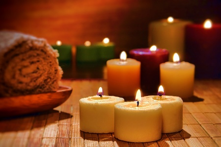 votive: Aromatherapy votive candles burning with a soft glow flame in dim light for a spiritual and wellness relaxation session in a spa