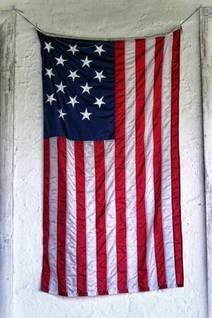 Grunge old USA antique American flag with fifteen stars hanging as a banner on the white wall of an ancient historic building