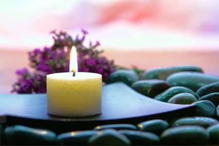 candle: Aromatherapy organic candle burning on a wood dish on a bed of rocks in a spa Stock Photo