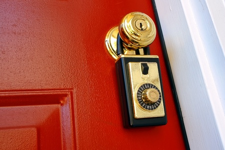combination lock: Realtor combination lock box safety key holder on doorknob of a house for sale entrance door for a real estate resale transaction   Stock Photo