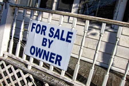 poorly: For sale by owner real estate sign hanging on front porch railing of poorly maintained old house
