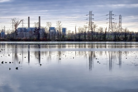 Coal fired electric energy generation plant with high voltage power transmission lines over wetland pond water landscape at dusk photo