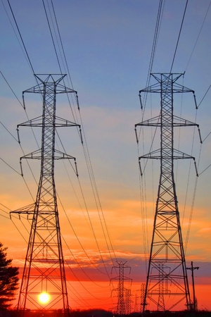 electric grid: Electric grid network power high voltage transmission lines pylon towers at sunset