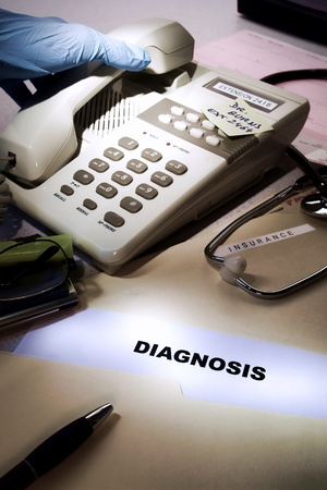 Medical dossier diagnosis tests results file folder on busy health care provider hospital desk and doctor hand with glove picking up the phone to call a patient with treatment prognosis