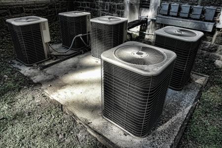 Batterij van HVAC airco compressor eenheden buiten een oud gebouw als onderdeel van een climate control koel-en vriesapparatuur conditioning systeem Stockfoto
