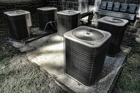 refrigerant: Battery of HVAC air conditioner compressor units outside an old building as part of a climate control cooling and refrigeration conditioning system Stock Photo