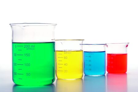 Graduated scientific beakers filled with assorted colors liquids for an experiment in a science research lab