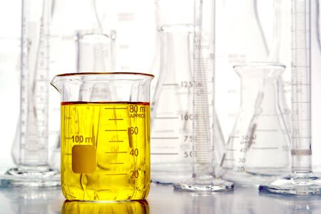 Graduated beaker filled with liquid and laboratory glassware for an experiment in a science research lab