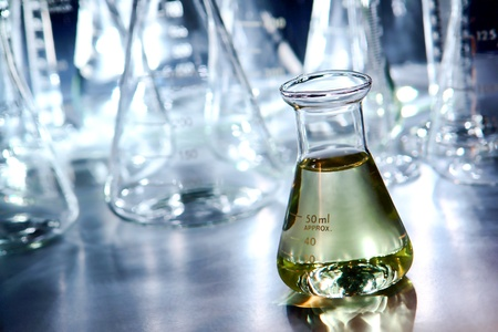erlenmeyer: Glass Erlenmeyer flask filled with liquid and laboratory glassware for an experiment in a science research lab
