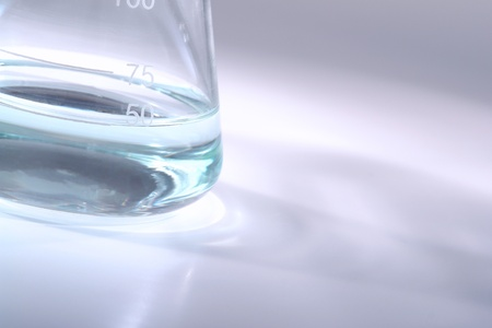 erlenmeyer: Glass Erlenmeyer flask with some liquid for an experiment in a science research lab Stock Photo