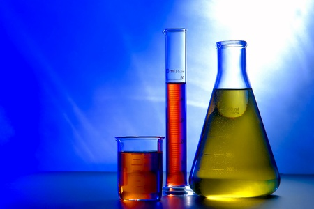Glass Erlenmeyer flask with beaker and graduated scientific cylinder filled with liquid for an experiment in a science research lab