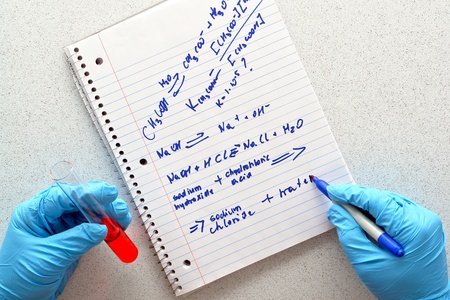 Scientist hand holding a test tube with red liquid and writing chemistry formulas on a notebook during an experiment in a science research lab photo
