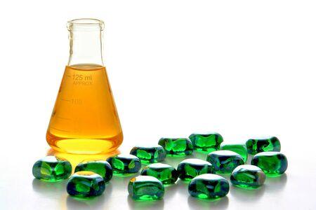 ガラス三角フラスコは、産業科学製造ラボで黄色の化学液体と緑のガラス玉でいっぱい