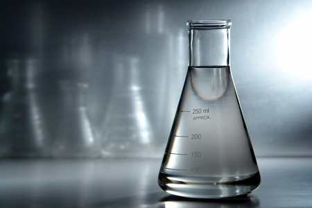 Glass Erlenmeyer flask filled with liquid for an experiment in a science research lab photo
