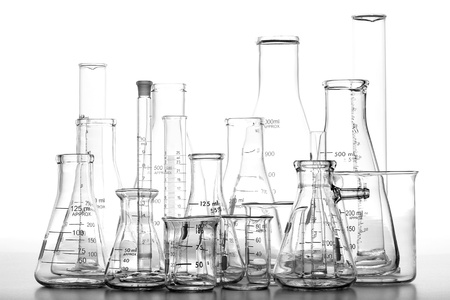 Assorted science laboratory glassware chemistry equipment featuring glass beakers with graduated scientific cylinders and Erlenmeyer flasks over white