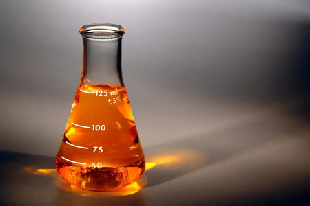 Scientific chemistry laboratory glass Erlenmeyer flask filled with gold amber color liquid for an experiment in a science research lab