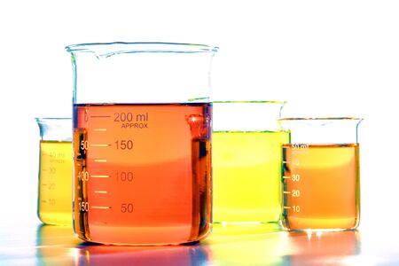 liquids: Assorted sizes glass scientific beakers filled with orange and yellow chemical liquids before a chemistry experiment in a science research lab
