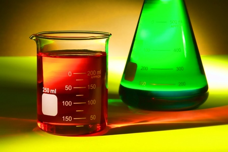 Glass scientific beaker filled with red chemical liquid and laboratory Erlenmeyer flask with green solution fluid for a chemistry experiment in a science research lab