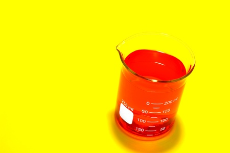 Laboratory glass scientific beaker filled with intense color red chemical liquid over bright saturated yellow background for a chemistry experiment in a science research lab