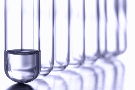 Test tube with small amount of chemical liquid at the bottom in a row of empty clear glass vessels for an applied discovery chemistry experiment in a science research lab Stock fotó