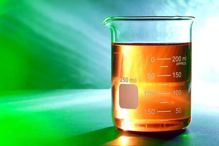 Afgestudeerd wetenschappelijke glazen beker met oranje oranje chemische vloeistof over reflecterende achtergrond voor een chemisch laboratorium experiment in een wetenschappelijk onderzoek lab