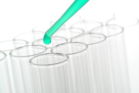 化学溶液ガラス研究所試験管バイオ サイエンス研究室で化学実験のための上の緑のドロップでピペットします。