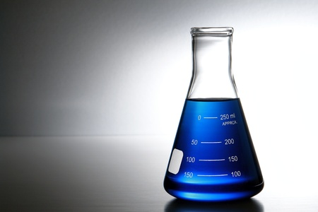 Laboratory glass Erlenmeyer conical flask filled with blue chemical liquid for a chemistry experiment in a science research lab photo
