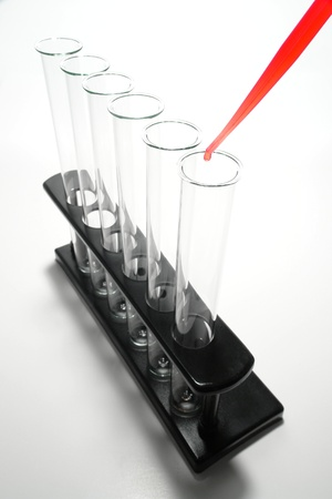 Pipette full of red liquid with hanging drop above empty laboratory test tubes on an equipment rack for a chemistry experiment in an applied research science lab