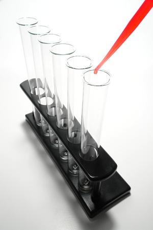 Pipetteer vol met rode vloeistof met opknoping druppel boven de lege laboratorium reageerbuisjes op een rek voor apparatuur voor een scheikunde experiment in een toegepast onderzoek Science Lab Stockfoto