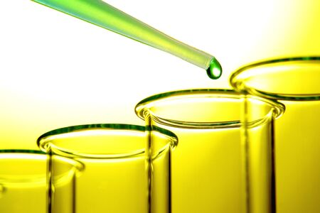 yellow lab: Laboratory pipette filled with green liquid and drop of chemical above empty test tubes backlit with yellow glow for a chemistry experiment in a science research lab Stock Photo