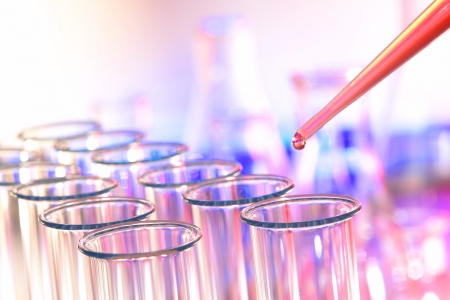 Laboratory pipette with drop of red chemical liquid hanging over rows of empty glass test tubes for a chemistry experiment in a busy science research lab
