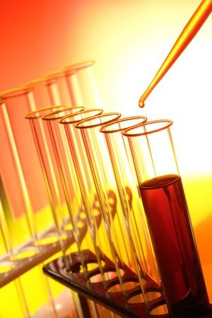 tubo de ensayo: Pipeta llena de líquido naranja con caída de químicos por encima de los tubos de ensayo de laboratorio vacía en un rack del equipo para un experimento de química en un laboratorio de investigación de Ciencias