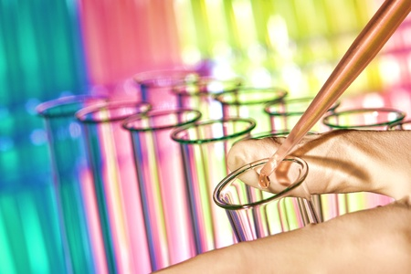 Pipette filled with red chemical and drop of liquid over laboratory glass test tubes in scientist hand for a chemistry experiment in a science research lab Standard-Bild