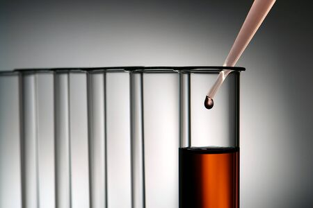 化学のテスト チューブの 2 行中淡い赤の化学溶液のドロップで研究室のピペット応用研究科学実験室での実験します。