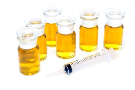 hormonas: Sin marcar botellas qu�micas llenados de �mbar l�quido soluci�n qu�mica como deporte ilegal rendimiento mejora anab�licos esteroides y jeringa de pl�stico en blanco