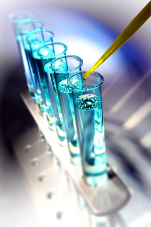 Pipette with drop of yellow chemical liquid over glass test tubes for an experiment in a science research lab