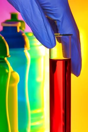 material de vidrio: Un tubo de ensayo de vidrio de laboratorio de mano científico llenos de solución líquida roja junto a las botellas coloridas para un experimento en un laboratorio de investigación de Ciencias