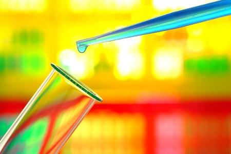 科学研究の実験室の実験のためのガラス試験管に青い液体化学溶液のドロップで研究室のピペット