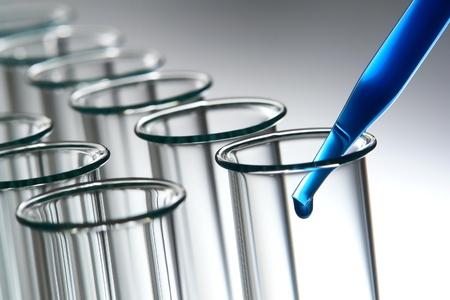 cristalería: Pipeta de laboratorio llenada de soluci�n qu�mica azul cobalto y emergente gota de l�quido en la fila de tubos de ensayo de vidrio vac�a para un experimento en un laboratorio de investigaci�n de Ciencias Foto de archivo