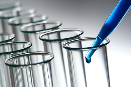 Laboratory pipette filled with cobalt blue chemical solution and emerging drop of liquid over row of empty glass test tubes for an experiment in a science research lab