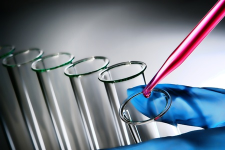 Laboratory pipette with drop of pink chemical liquid over glass test tube held in scientist hand for an experiment in a science research lab