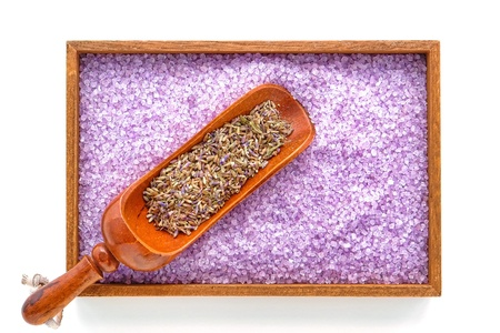 salts: Dry lavender flower seeds in a traditional wood scoop on a wooden tray filled with scented purple natural bath salts crystals in an aromatherapy spa over white background  Stock Photo