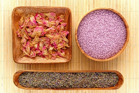 Aromatherapy natural ingredients of lavender seeds and scented dried flower petals with aromatic bath soap salts in wood bowls for a pampering and soothing body care relaxation session in a spa Stock Photo - 10666327