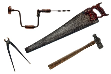 drill bit: Antique collection of vintage tools with distressed blacksmith hammer and carpenter crosscut handsaw with carpenter hand crank brace with bit drill and retro pair of used pincer cutting pliers tool isolated on white